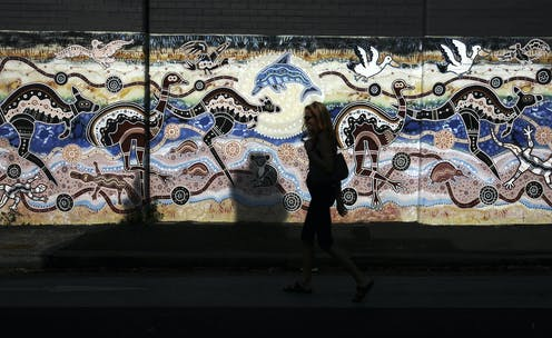 A woman passes an Aboriginal styled mural on a wall in Newtown, Sydney.