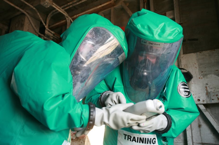Two US Marines in green hazmat suits taking part in a bioweapon defense training