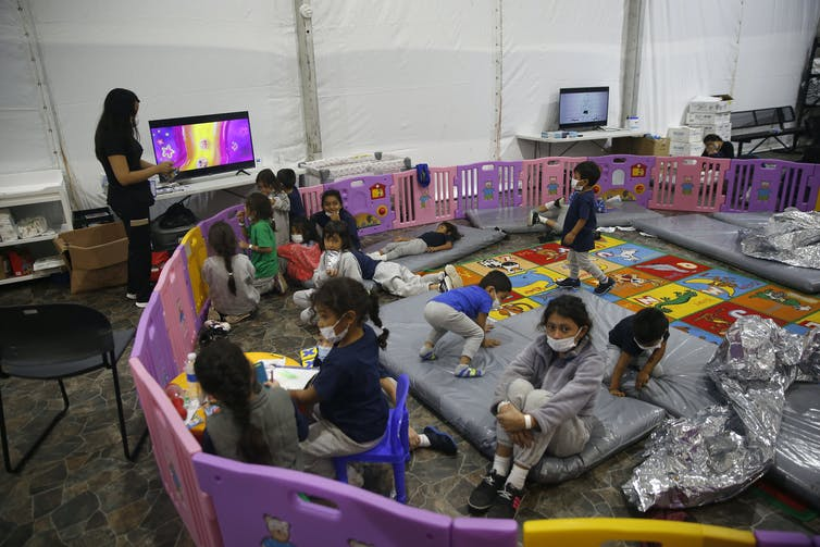 Young children watch TV inside a pen in the federal government's holding facility in Donna, Texas.