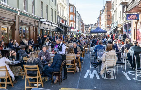 People in groups dining outside in central London
