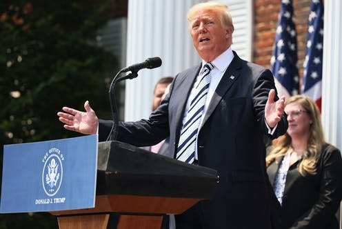 Donald Trump at a lectern speaking into a microphone and gesturing with his hands.