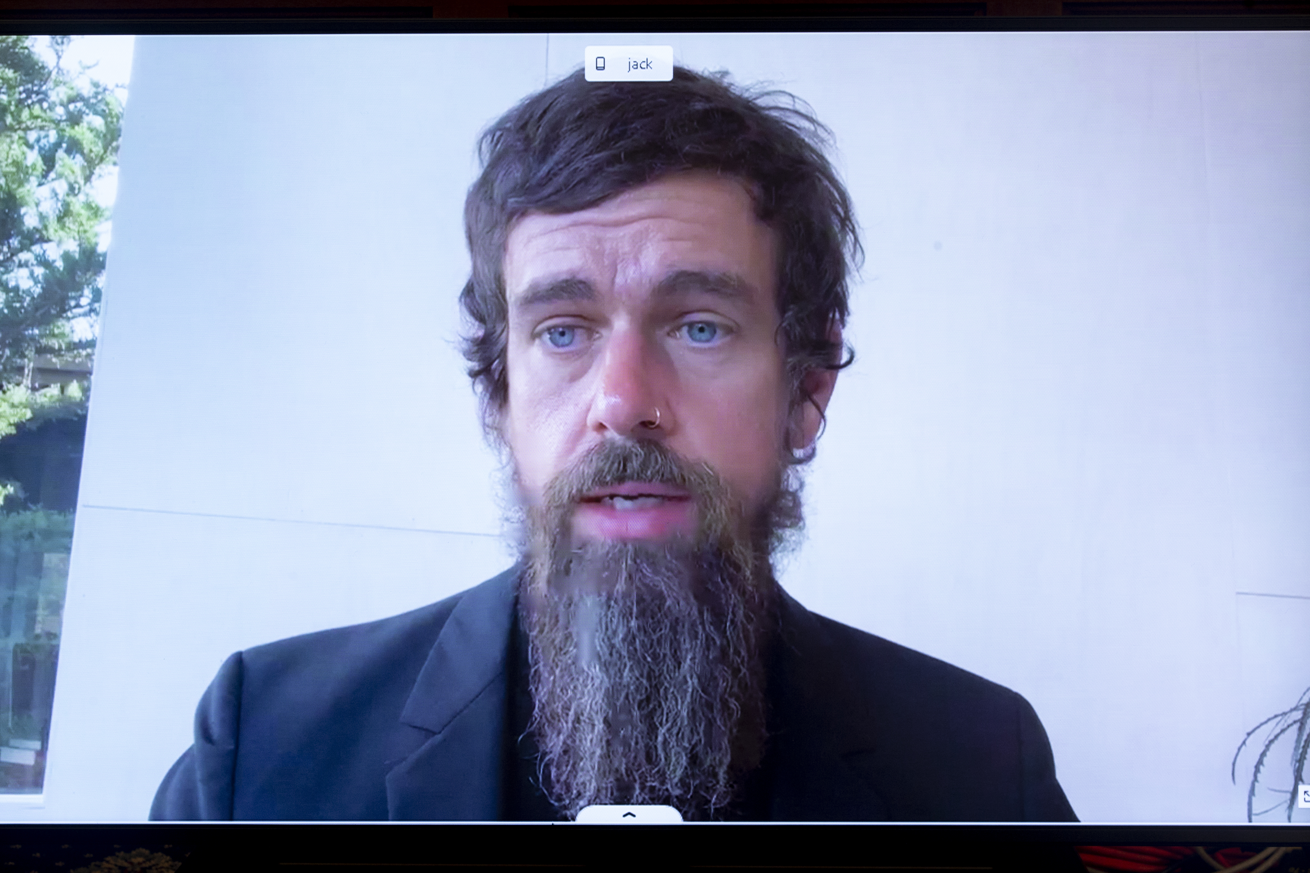 Twitter CEO Jack Dorsey, a man with bright blue eyes, brown hair and a wiry hipster beard, speaking on a monitor.