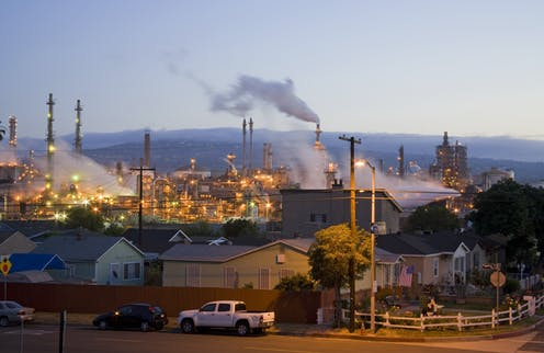 Homes next to a lit-up oil refinery in Wilmington, California.