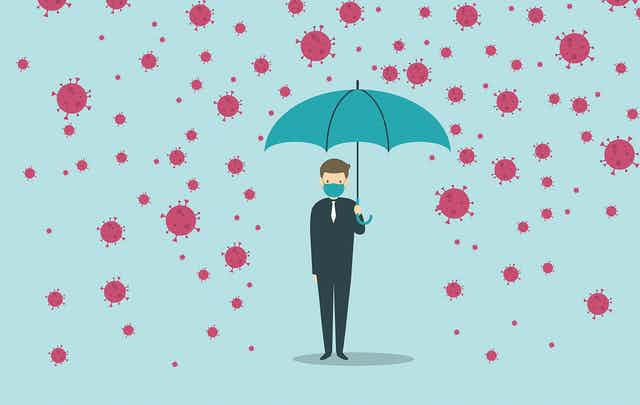 A man holding an ubrella underneath raining coronavirus particles.
