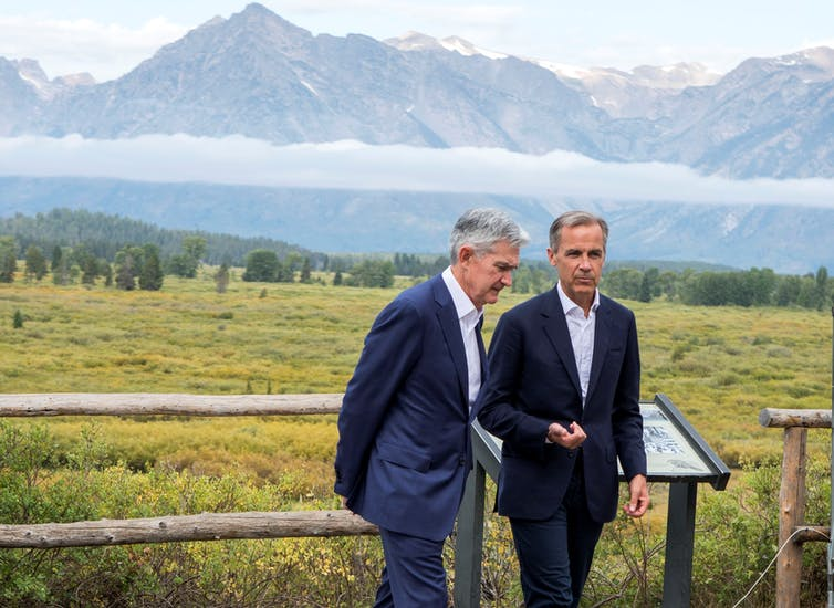 Jerome Powell and Mark Carney talk at a conference at Jackson Hole, Wyoming, with mountains behind them.