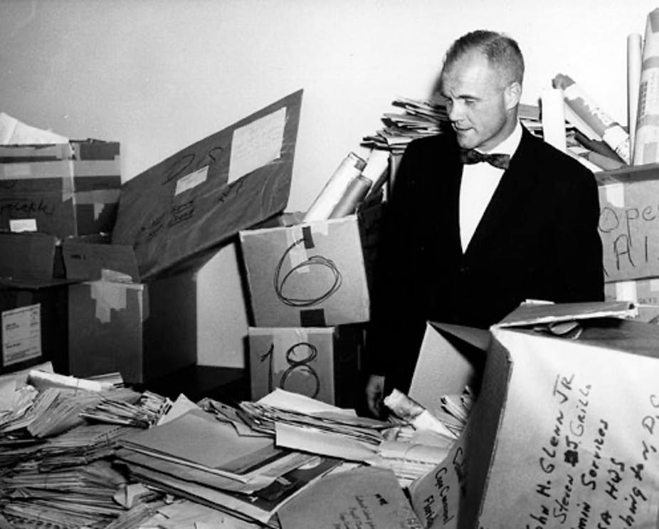 Glenn stands amid piles of mail