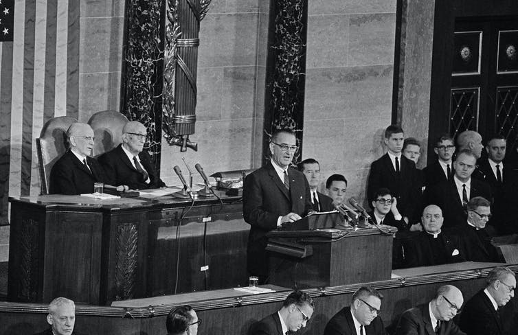 President Lyndon B. Johnson delivers his State of the Union address to a joint session of Congress in the House of Representatives as lawmakers and other look on.