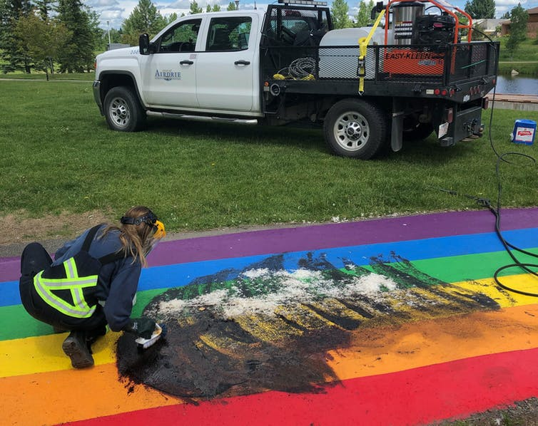 A worker cleans a rainbow path on the ground that has been vandalized.
