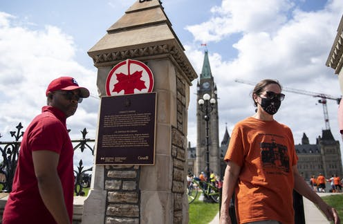 A man in red shirt stands in front of upside down maple leaf next to woman in orange shirt.