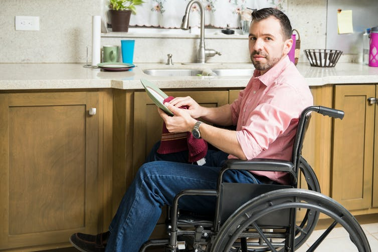 A man in a wheelchair drying a plate in the kitchen.