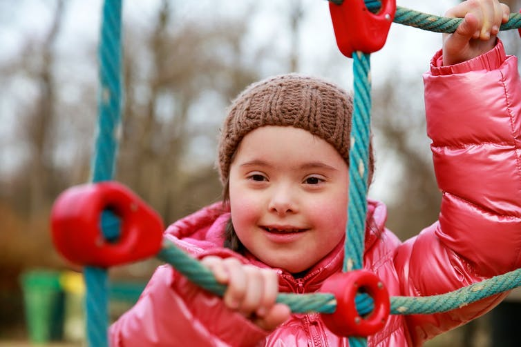 A girl smiling in the playground.