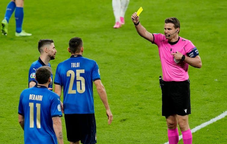 A footballer receives a yellow card.