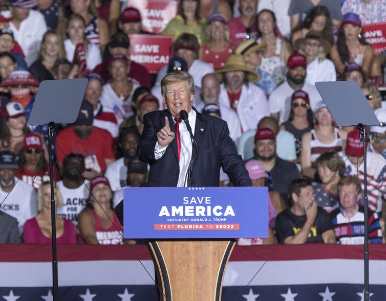 Former US President Donald Trump speaking at a rally. There is a Save America placard on his podium, and he has one finger raised.