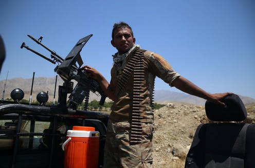 An Afghan soldier manning an armoured vehicle with a bandoleer of ammunition around his neck.
