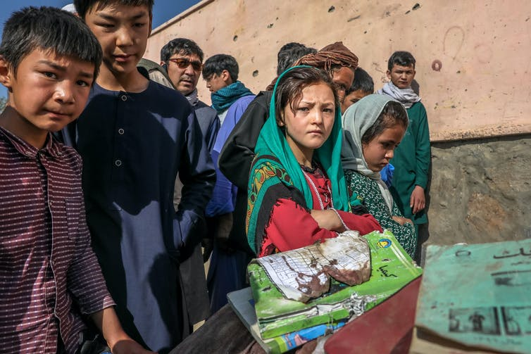 Yojg girls and boys with bloodstained school books and belongings of pupils killed in a car bomb attack on a Kabul high school, May 2021.