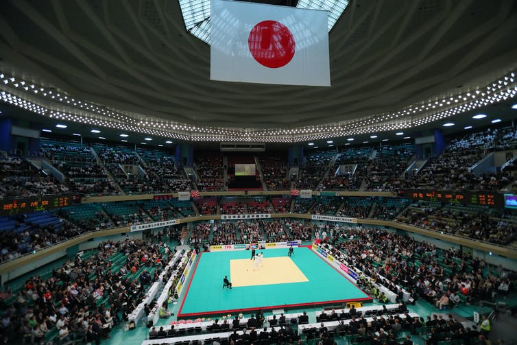 Seated crowds in an arena watch a judo match with Japanese flag above