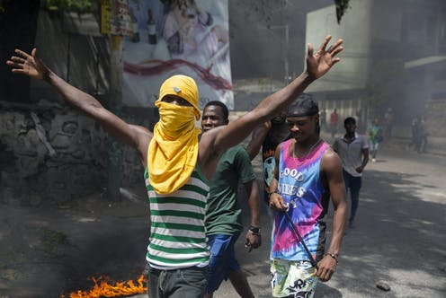 Jeunes hommes manifestant dans une rue, l'un d'eux masqué