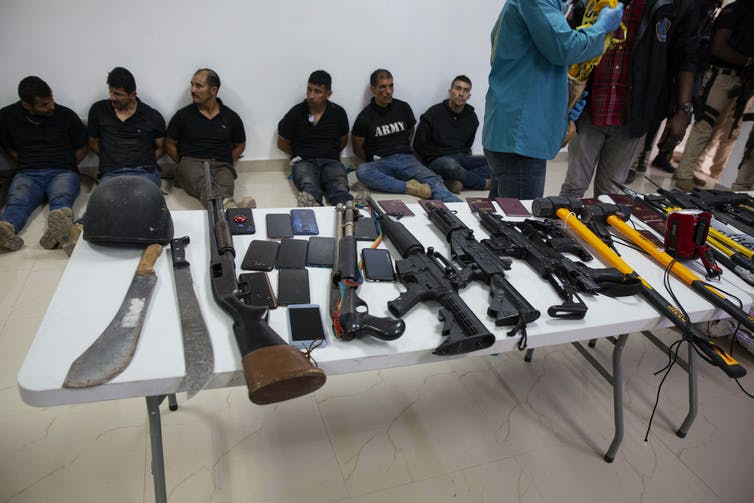 Weapons on a table, including machetes and assault rifles. Behind them, a row of men sit.