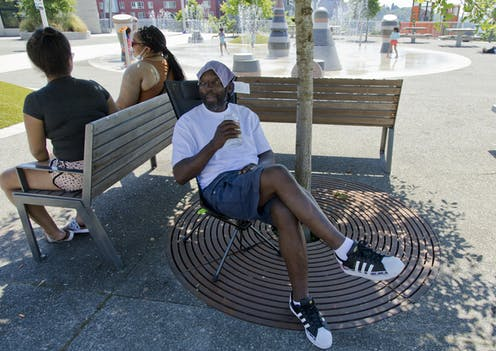 A Black man in shorts and a T-shirt sits under a tree. He is drinking water and has a cloth on his head. In the background, children play in a spray park.