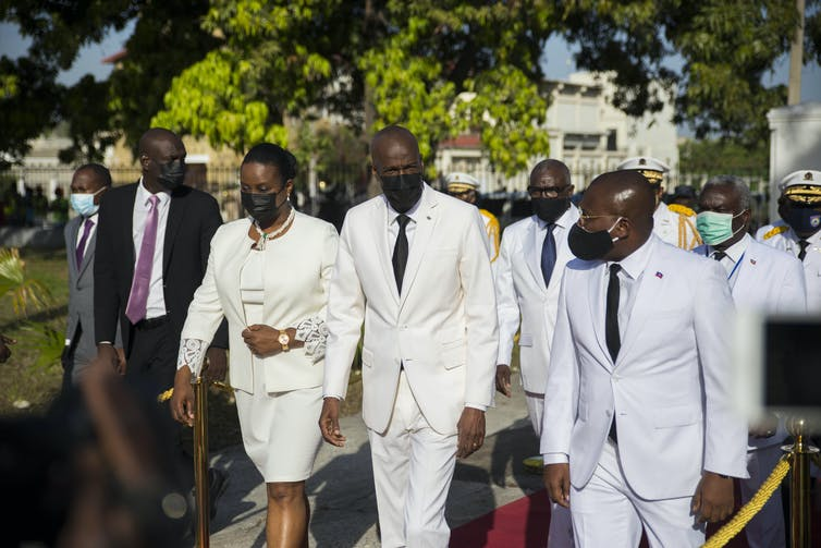Haiti's President Jovenel Moïse and his wife, Martine, walk during a ceremony