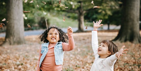 Two children throwing leaves in the air.