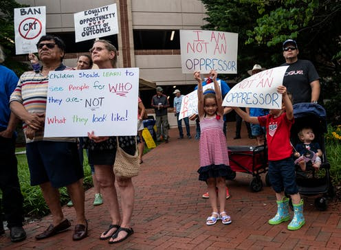 A group of protestors hold signs against the teaching of critical race theory in schools.