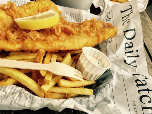 Fried cod on a bed of chips with a slice of lemon and tartare sauce wrapped in newspaper.