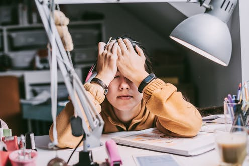 A student rests their head against their hands on a cluttered desk.