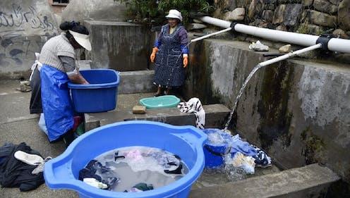 Dos mujeres de los pueblos indígenas de Bolivia lavan su ropa en un lavadero municipal con agua de lluvia en La Paz, el 12 de septiembre de 2019.
