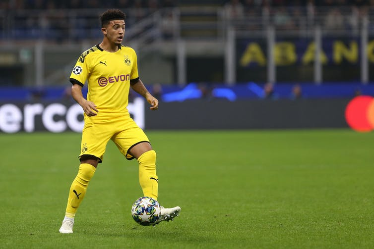 Footballer in yellow kit kicking a ball.