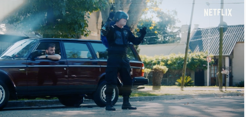 A man in a superhero outfit stands next to a car