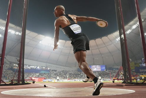 Full-body shot of an athlete in the middle of a discus throw with a full stadium in the background