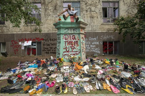 Spray paint reads 'dig them up' '215' and 'shame' with a bunch of shoes in the foreground