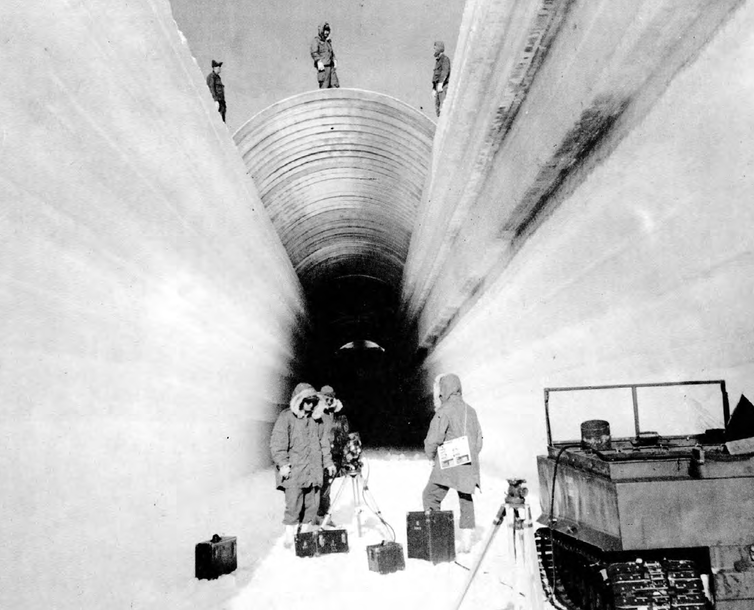 Three people stand at the opening of a trench with a half-round metal cover