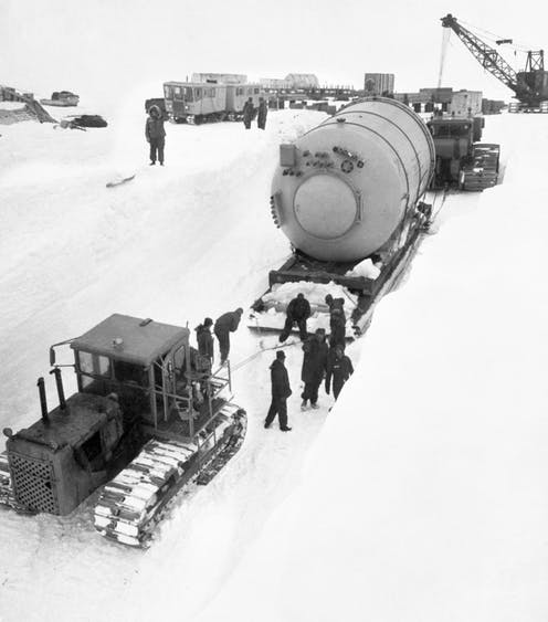 A large condenser on a sled is moved by tractor across the snow and ice