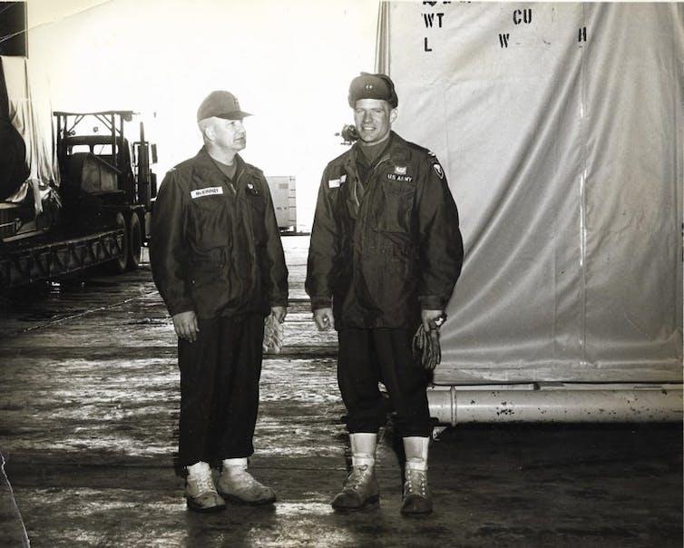 Two men in uniform standing in a hangar.
