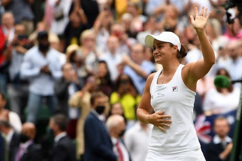 Ashleigh Barty waves to the Wimbledon crowd.