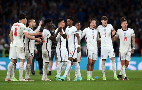 Row of England footballers on pitch high-fiving Marcus Rashford.