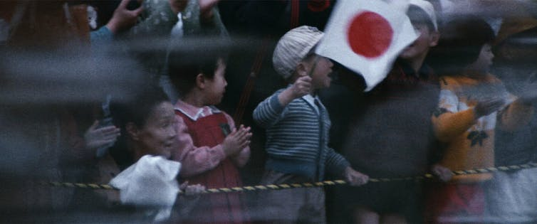 A young boy waves the Japanese flag