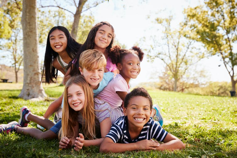 A group of children piled on top of each other in a park.