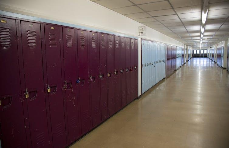 Long rows of lockers in an empty school hallway