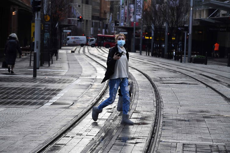 A woman crosses a deserted street in the Sydney CBD.
