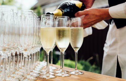 A waiter pours champagne into multiple champagne flutes