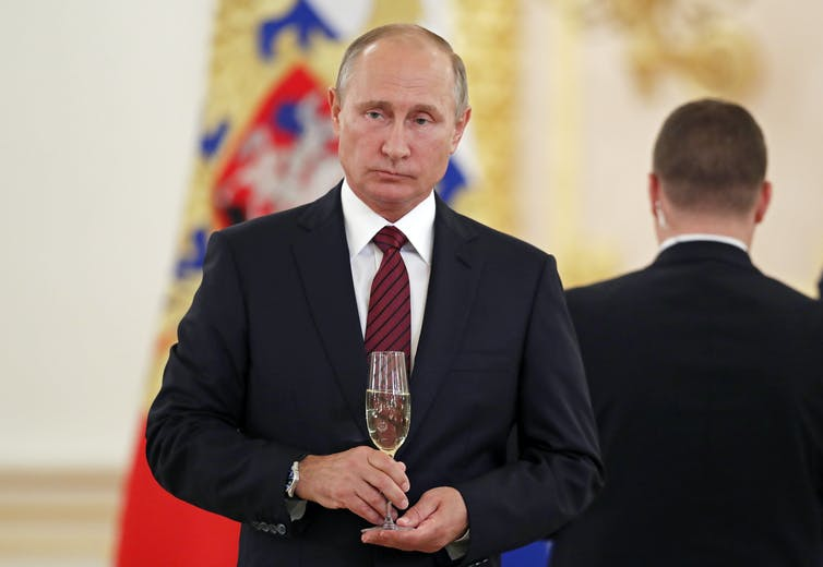 Russian President Vladimir Putin holding a glass of champagne at an event.