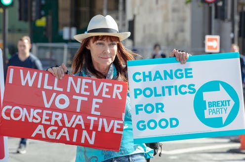 """A woman holds two placards: One says """"I will never vote conservative again,"""" the other reads """"Change politics for good: Brexit Party"""