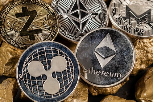 Metal coins featuring the logos of altcoins