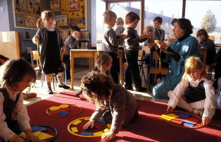 Primary school pupils play with coloured shapes on a red carpet