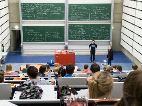 Students in an auditorium look down at professors and a wall of blackboards covered in mathematical formulae