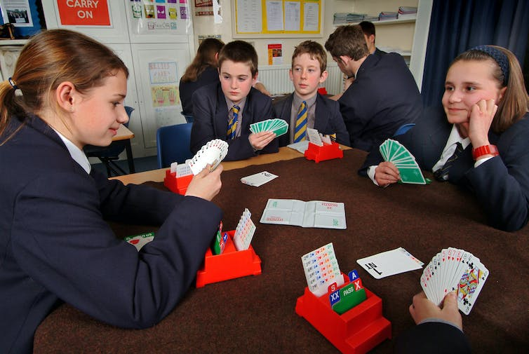 Secondary school pupils play cards in a maths lesson