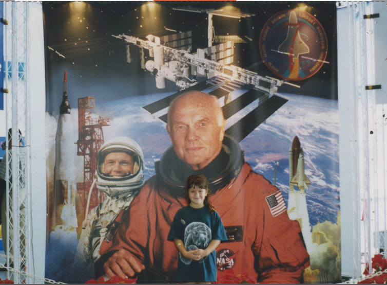 smiling girl stands in front of a John Glenn space mural